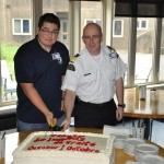 (L-R) Levi Paul, a first year Coast Guard Marine Engineering Cadet  from Potlotek (Chapel Island) cuts the celebratory cake with Brian LeBlanc, Executive Director of the Coast Guard College in Sydney.