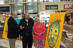 (L-R) Peter Spurway, the airport's vice-president of corporate communications and airport experience; Alan Syliboy, Mi'kmaw artist; and Lenore Zann, Truro-Bible Hill MLA look over one of Alan's paintings. Photo by Communications Nova Scotia