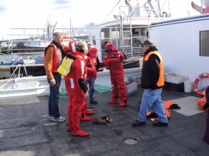Fish SAFE and NSCC School of Fisheries Safety Advisors oversee the crew of the Annapolis Valley First Nation vessel Lobster Stalker as they put on their cold water immersion suits during an abandon ship emergency response drill. (L-R) Steve Grant (Captain of Lobster Stalker), John Krgovich (Fish SAFE Safety Advisor), Keith Maillet (Deckhand on Lobster Stalker), Joe Grandy (NSCC School of Fisheries Safety Advisor), Gina MacKay (Fish SAFE Program Manager), Blair Campbell (NSCC School of Fisheries Safety Advisor), Fred Phillips (Deckhand of Lobster Stalker), and Jerry Toney (Fisheries Coordinator of Annapolis Valley First Nation).