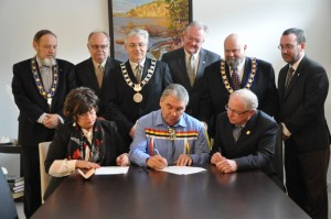 Municipal leaders gather around to sign the agreement marking the establishment of the Valley Regional Enterprise Network, an agency devoted to driving economic development within the region. (Back L-R) Bridgetown Mayor Horace Hurlburt, Middleton Mayor Calvin Eddy, Windsor Mayor Paul Beazley, Wolfville Mayor Jeff Cantwell, Kentville Mayor David Corkum and Hantsport Mayor Rob Zwicker; (Front L-R) Diana Brothers, warden of the County of Kings, Glooscap First Nation Chief Sidney Peters and Richard Dauphinee, warden for the Municipality of West Hants. Photo by Ashley Thompson