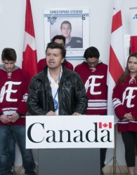 Eskasoni Chief, Leroy Denny addressed the public and media during the rink funding announcement held at the Eskasoni high school. A few members of the Eskasoni Coyote high school hockey team were in the background for the special announcement. Photo by George Paul