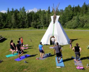 "A free Yoga session was provided by Catherine Knockwood at Millbrook's Powwow grounds on July 4, 2016. In the photo you can see Catherine (Top Center) leading the class in the ""Tree Pose"". Photo by Currie Cinemedia"